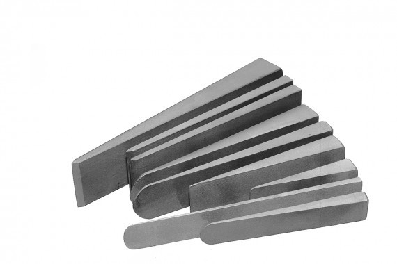 A set of steel hand splitting wedges used for stone splitting laid out together